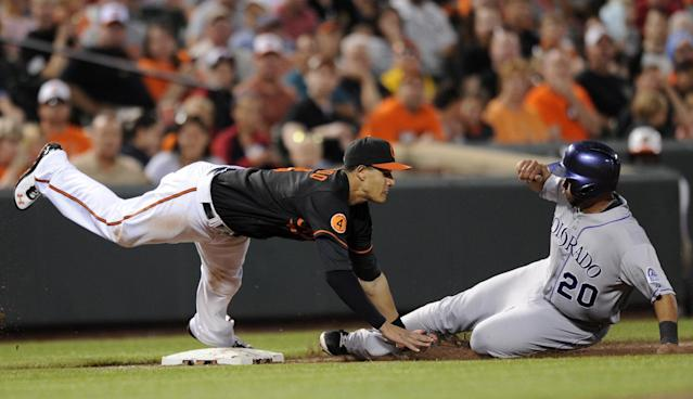 Colorado Rockies' Wilin Rosario (20) slides into third safely on a wild pitch against the Baltimore Orioles third baseman Manny Machado (13) during the fifth inning of a baseball game, Friday, Aug. 16, 2013, in Baltimore. (AP Photo/Nick Wass)