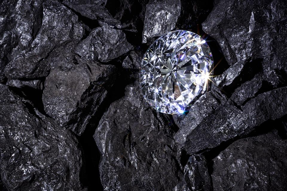 A single solitaire Diamond in amongst some pieces of coal.