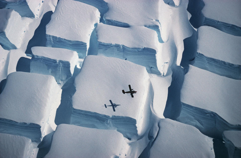 <p>The photo, taken in early 1995 during a flight over the English Coast (southern Antarctic Peninsula) at about 74 degrees south, illustrates the scale of unusual bi-directional crevassing as an ice sheet is stretched in two directions over an underlying rise, with a Twin Otter aeroplane as scale. It was named as Overall winner and winner in the Earth Science and Climatology category. (PA) </p>