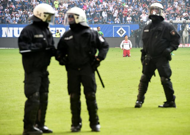 Soccer Football - Bundesliga - Hamburger SV v Borussia Moenchengladbach - Volksparkstadion, Hamburg, Germany - May 12, 2018 Hamburg's Tatsuya Ito looks dejected at the end of the match as riot police are on the pitch REUTERS/Fabian Bimmer DFL RULES TO LIMIT THE ONLINE USAGE DURING MATCH TIME TO 15 PICTURES PER GAME. IMAGE SEQUENCES TO SIMULATE VIDEO IS NOT ALLOWED AT ANY TIME. FOR FURTHER QUERIES PLEASE CONTACT DFL DIRECTLY AT + 49 69 650050
