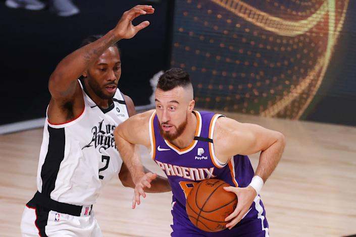 "Phoenix Suns' Frank Kaminsky drives against Clippers' Kawhi Leonard on Tuesday in Lake Buena Vista, Fla. <span class=""copyright"">(Kevin C. Cox / Associated Press)</span>"