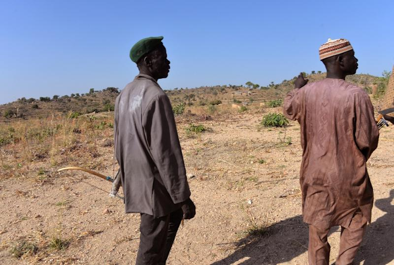 A picture taken on February 16, 2015 shows members of a self-appointed vigilance committee hunting down and fighting Boko Haram Islamic group, walking in the village of Lding Lding, northern Cameroon