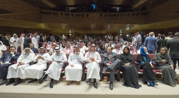 A handout picture provided by the Saudi Royal Palace on April 18, 2018, shows Saudi Information Minister Awwad Alawwad, center, holding a small bucket of popcorn as he attends a test screening at the AMC cinema in Riyadh.