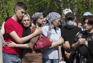 People react next to the grave of Elvira Ignatieva, an English language teacher who was killed at a school shooting on Tuesday in Kazan, Russia, Wednesday, May 12, 2021. Russian officials say a gunman attacked a school in the city of Kazan and Russian officials say several people have been killed. Officials said the dead in Tuesday's shooting include students, a teacher and a school worker. Authorities also say over 20 others have been hospitalised with wounds. (AP Photo/Dmitri Lovetsky)