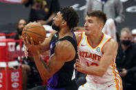 Toronto Raptors center Khem Birch (24) gets fouled by Atlanta Hawks guard Bogdan Bogdanovic (13) during the first half of an NBA basketball game Tuesday, April 13, 2021, in Tampa, Fla. (AP Photo/Chris O'Meara)