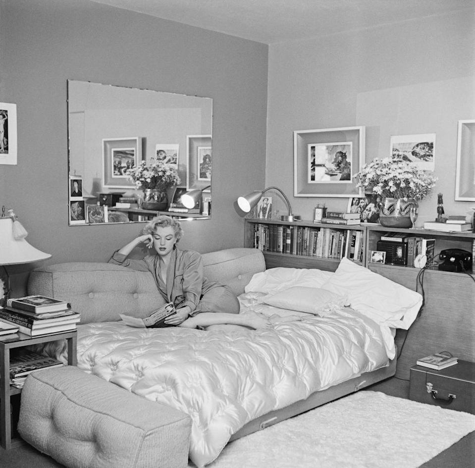 """<p>At the start of her career, Marilyn Monroe was photographed cozying up on a sofa bed to read a book in 1951. Although it's unclear where Marilyn is staying in this photo, the model and actress <a href=""""https://www.discoverlosangeles.com/things-to-do/discover-marilyn-monroes-los-angeles"""" rel=""""nofollow noopener"""" target=""""_blank"""" data-ylk=""""slk:lived in the Hollywood Roosevelt Hotel"""" class=""""link rapid-noclick-resp"""">lived in the Hollywood Roosevelt Hotel</a> around this time.</p>"""