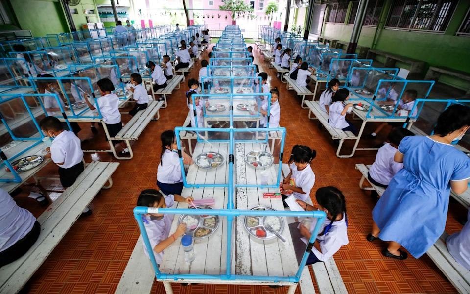 Students eat their lunch, separated from each other by plastic sheets in Bangkok - DIEGO AZUBEL/EPA-EFE/Shutterstock