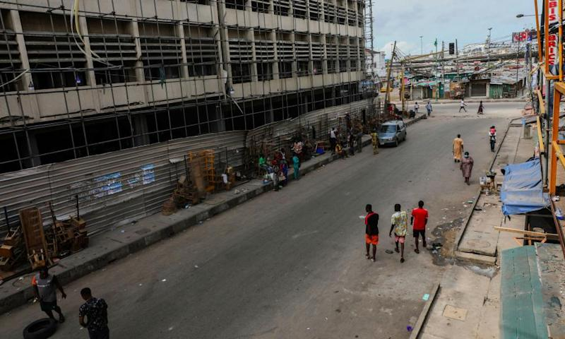 People walk along a closed market during lockdown in Lagos.
