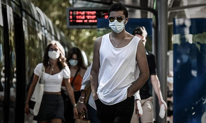 Commuters wearing protective face masks due to the Covid-19 pandemic walk out of a tramway platform in Bordeaux, south-west France.