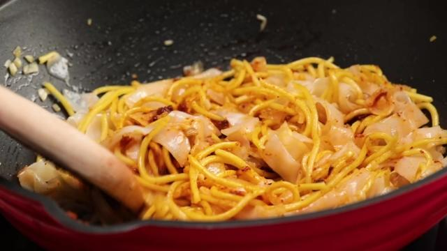 Frying yellow noodles and kway teow in a pan with wooden spatula