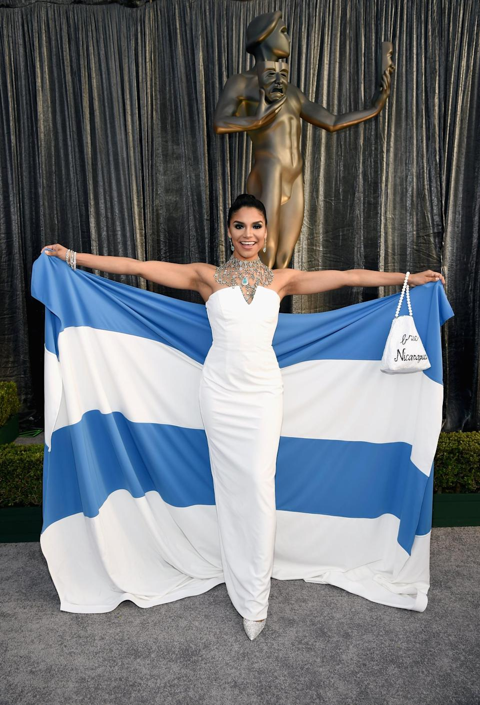 <p>Wearing a white gown with the flag of Nicaragua.</p>