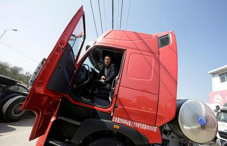 Sales manager Nie Liliang speaks while sitting in a liquefied natural gas (LNG) truck outside a heavy-duty truck shop in Yutian county, China's Hebei province September 29, 2017. REUTERS/Jason Lee