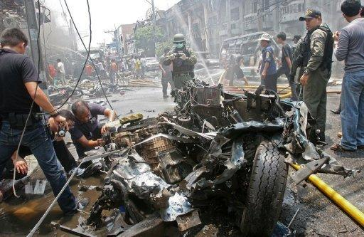 Thai bomb squad members inspect the wreckage of a car at the scene of a car bomb blast in Thailand's southern restive province of Yala. Three bomb attacks minutes apart killed 10 people and wounded more than 100 in the main town in Thailand's insurgency-hit far south
