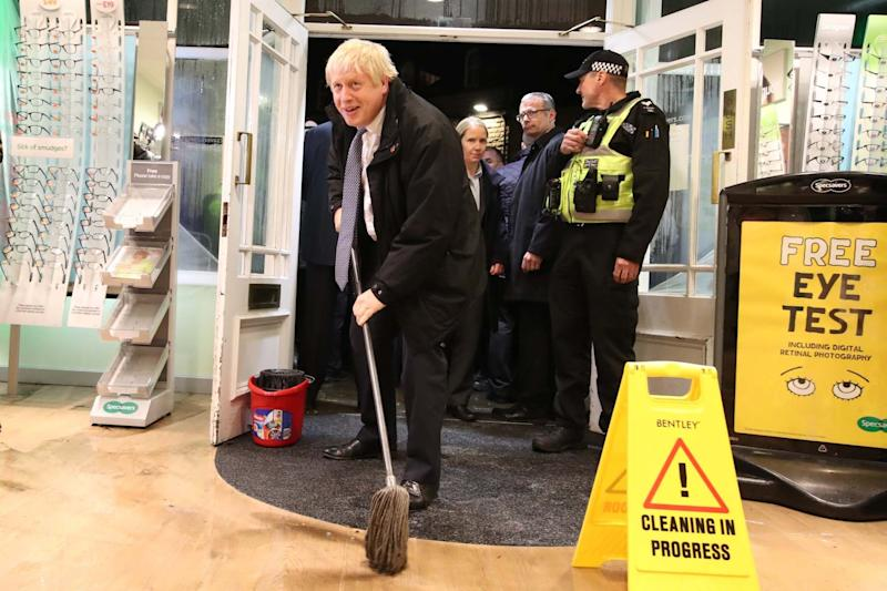 Prime Minister Boris Johnson helps with the clean up at an opticians as he visits Matlock on November 8: Getty Images
