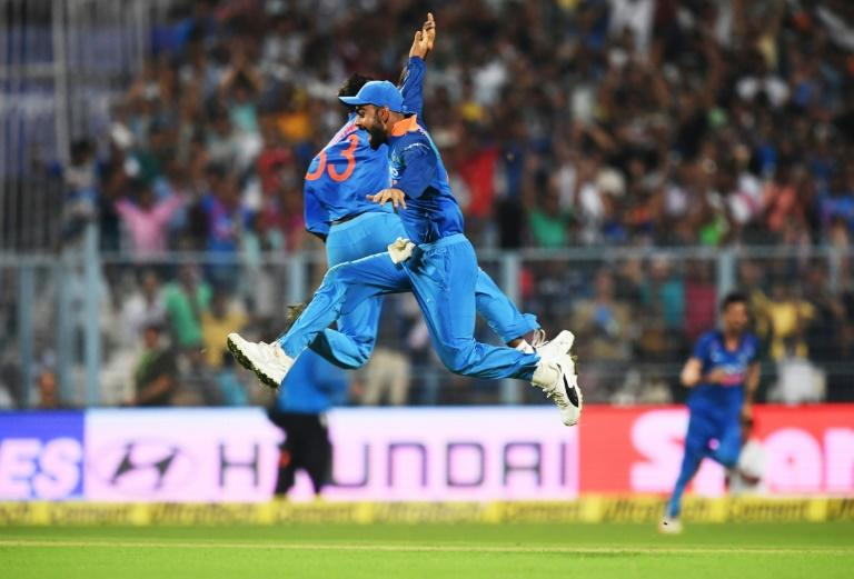 India's captain Virat Kohli (R) and teammate Hardik Pandya celebrate the wicket of Australia's captian Steve Smith during the second one day international match of the ongoing India-Australia cricket series at the Eden Gardens Cricket Stadium in Kolkata (AFP Photo/Dibyangshu SARKAR)
