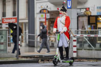 A carnival reveller rides an electric scooter near the Severinstor gate in Cologne, Germany, Monday, Feb. 15, 2021. Because of the coronavirus pandemic the traditional carnival parade in the city are canceled. (Rolf Vennenbernd/dpa via AP)
