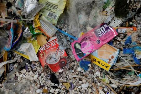 Sachets of Nestle's Nescafe coffee and Unilever's Sunsilk shampoo are pictured amidst a garbage-filled shore on Freedom Island, Paranaque City