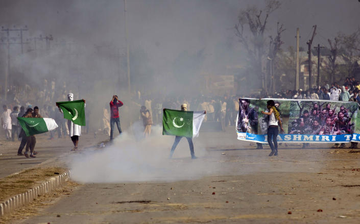 FILE - In this Sept. 25, 2015,file photo, masked Kashmiris hold a national flag of Pakistan and a banner displaying militant leaders of the Hizb-ul Mujahedeen during a protest outside Eidgha, a prayer ground, in Srinagar, Indian controlled Kashmir. India's leaders are anxiously watching the Taliban takeover in Afghanistan, fearing that it will benefit their bitter rival Pakistan and feed a long-simmering insurgency in the disputed region of Kashmir, where militants already have a foothold. (AP Photo/Dar Yasin, File)