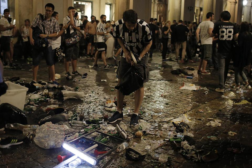 <p>Juventus' supporters look for personal belongings in Piazza San Carlo after a panic movement in the fanzone where thousands of Juventus fans were watching the UEFA Champions League Final football match between Juventus and Real Madrid on a giant screen, on June 3, 2017 in Turin. (Massimo Pinca/AFP/Getty Images) </p>