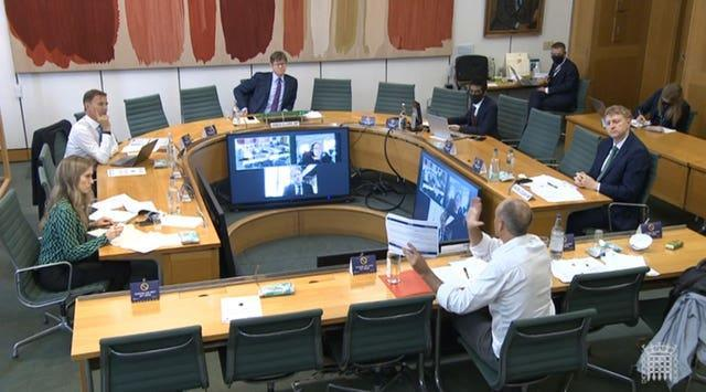 Dominic Cummings, former chief adviser to Prime Minister Boris Johnson, holds up a document while giving evidence to a joint inquiry of the Commons health and social care and science and technology committees