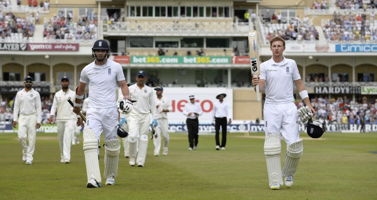 England's James Anderson and Joe Root (R) leave the field for the lunch break, after breaking the record for the highest tenth wicket partnership in test cricket, during the first cricket test match against India at Trent Bridge cricket ground in Nottingham, England July 12, 2014. REUTERS/Philip Brown (BRITAIN - Tags: SPORT CRICKET)