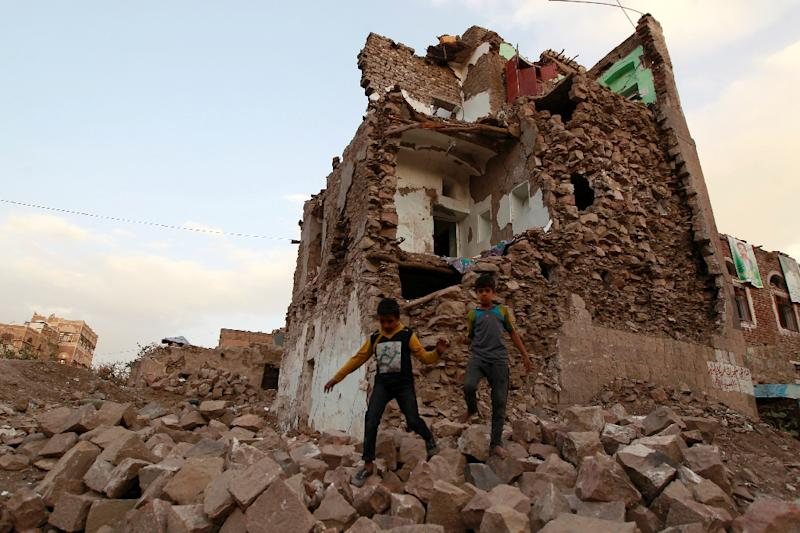 Yemeni children walk on stones in front of buildings that were damaged by air strikes carried out by the Saudi-led coalition over the past year in the Yemeni capital Sanaa on March 23, 2016 (AFP Photo/Mohammed Huwais)