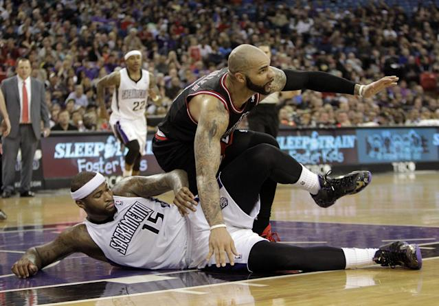 Sacramento Kings center DeMarcus Cousins, left, hits the floor as he is fouled by Chicago Bulls forward Carlos Boozer during the third quarter of an NBA basketball game in Sacramento, Calif., Monday, Feb. 3, 2014. The Kings won 99-70. (AP Photo/Rich Pedroncelli)
