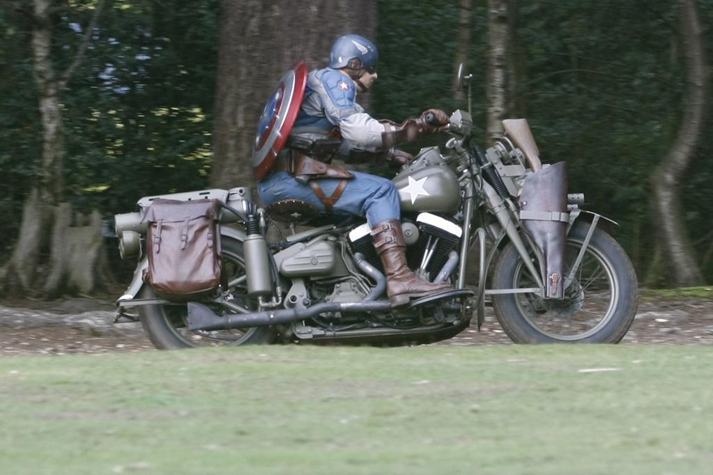 This is the first actual photo of Captain America's costume, but it's a stunt double wearing it, not Evans. The suit is less streamlined and more utilitarian than how Cap is usually depicted in the comics, but he does have his classic shield slung over his back. He rides an American military motorcycle from the WWII era.