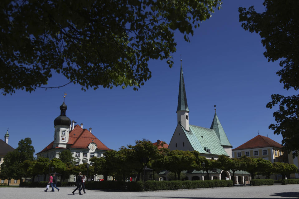 """People across the main square 'Kapellplatz"""" in Altoetting, some 90 kilometers (about 55 miles) east of Munich, Germany, Thursday, May 7, 2020. """"The heart of Bavaria and one of the hearts of Europe"""". Pope emeritus Benedict XVI. said. The city is one of the 'Shrines of Europe', the seven most important Marian pilgrimage sites in Europe. The 'Graminger Weissbraeu' brewery and traditional Bavarian restaurant, which has been in the same family for a century, is preparing to welcome guests back to its restaurant for the first time in two months — with new rules and fears for the future. (AP Photo/Matthias Schrader)"""