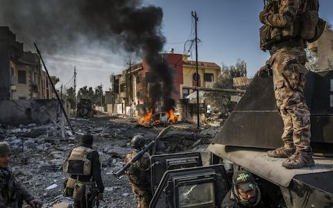 Iraqi Special Forces soldiers surveyed the aftermath of an Isil suicide car bomb that managed to reach their lines in the Andalus neighbourhood, one of the last areas to be liberated in east Mosul - Credit: Ivor Prickett/The New York Times