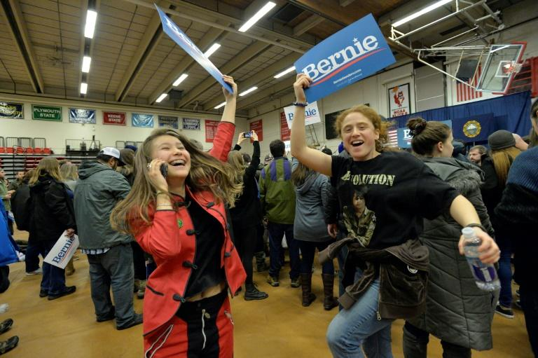 Supporters of US Presidential Candidate Senator Bernie Sanders cheer and wave campaign signs as they await his arrival at a campaign rally at Keene State College in Keene, New Hampshire on February 9, 2020