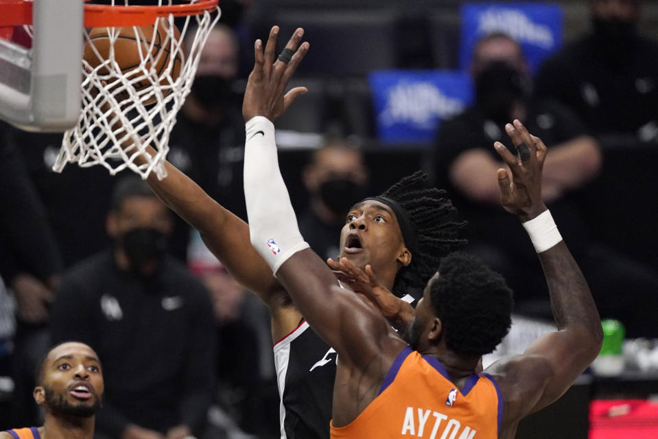 Los Angeles Clippers guard Terance Mann, top, shoots as Phoenix Suns center Deandre Ayton defends during the second half in Game 3 of the NBA basketball Western Conference Finals Thursday, June 24, 2021, in Los Angeles. (AP Photo/Mark J. Terrill)