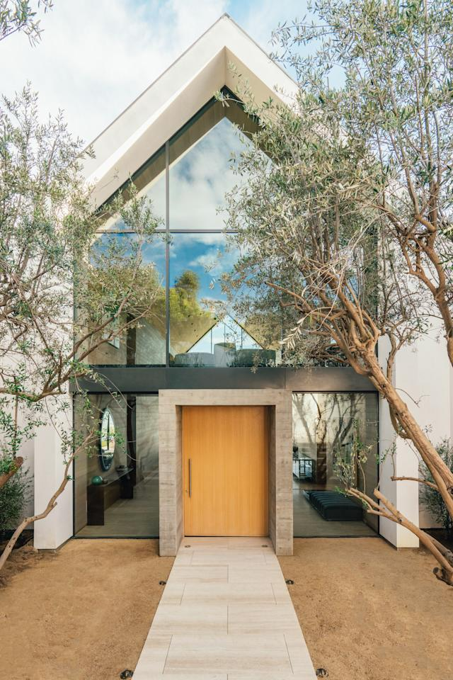 """The house is tall and the space was tight, so creating a meaningful entry experience was the biggest challenge,"" says Allsbrook. ""Arriving at the house, you descend into a small courtyard that has a more intimate scale. We framed the door in a concrete cube flanked by two mature olive trees. These elements bring a human scale to the house and precede the drama of the interior height."""