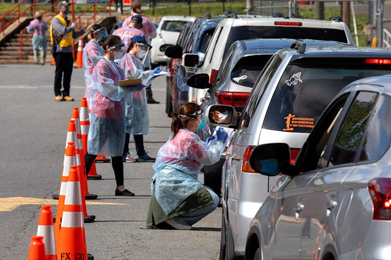 A man wearing a facemask waits inside his car to be tested for COVID-19 as volunteers take registration information in Annandale, Va., Saturday, May 23, 2020. COVID-19 testing was available from Fairfax County at no cost and without a doctor's order. Hundreds of people had lined up in cars and on foot by 10am. Officials planned on testing about 1000 people from 10 a.m. to 6 p.m. Testing will be available at Bailey's Elementary on Sunday. (AP Photo/Jacquelyn Martin)