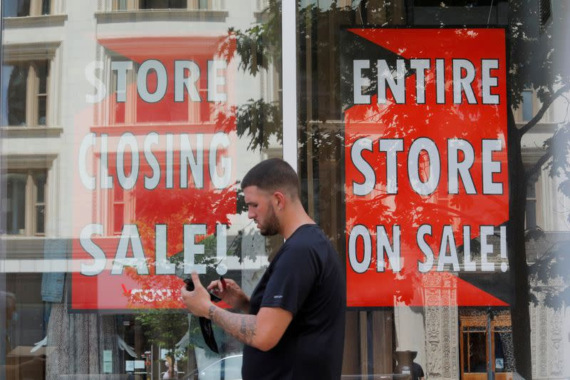 FILE PHOTO: A man walks past signs in the windows of Lord & Taylor, advertising a store closing sale, in Boston
