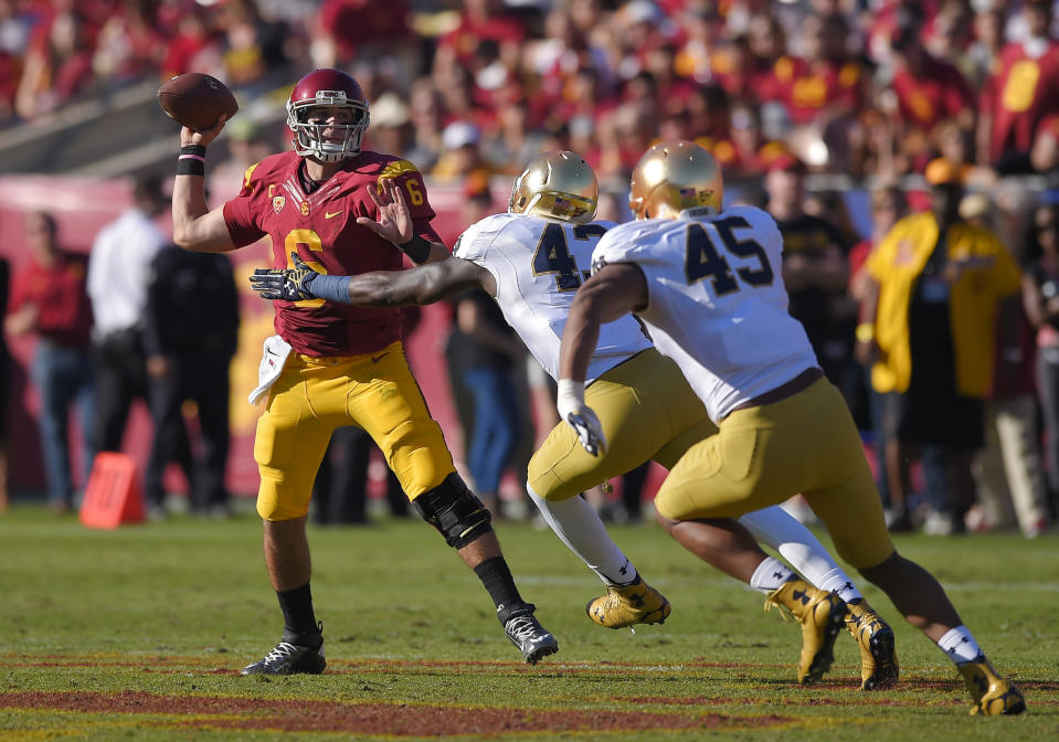 Southern California quarterback Cody Kessler, left, passes under pressure from Notre Dame linebacker Kolin Hill, center, and defensive lineman Romeo Okwara during the first half of an NCAA college football game, Saturday, Nov. 29, 2014, in Los Angeles. (AP Photo/Mark J. Terrill)