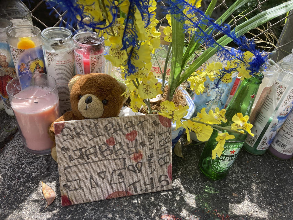 FILE - In this April 28, 2021, file photo, a stuffed bear sits with other tributes at a street memorial where Honolulu Police shot and killed 16-year-old Iremamber Sykap, whose nickname was Baby, during a car chase on Kalakaua Ave. in Honolulu. Three Honolulu police officers asked a judge on Tuesday, July 6, 2021, to dismiss charges against them in connection with a shooting that killed Sykap. (AP Photo/Jennifer Sinco Kelleher, File)