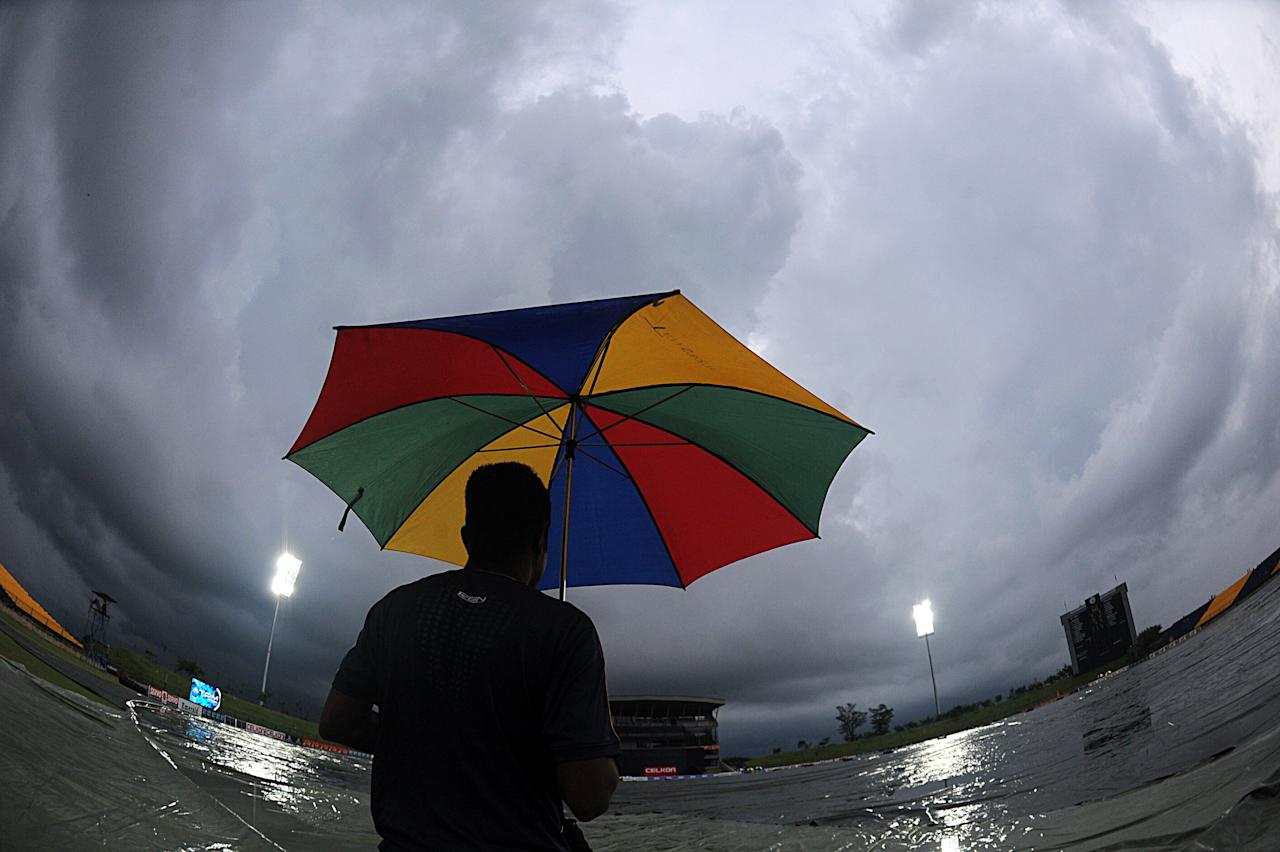 A Sri Lankan man holds an umbrella as he walks across the covers on the pitch after rain stopped play during the second One-Day International (ODI) match between Sri Lanka and Bangladesh at The Suriyawewa Mahinda Rajapakse International Cricket Stadium in the southern district of Hambantota on March 25, 2013.  AFP PHOTO/ Ishara S. KODIKARA        (Photo credit should read Ishara S.KODIKARA/AFP/Getty Images)