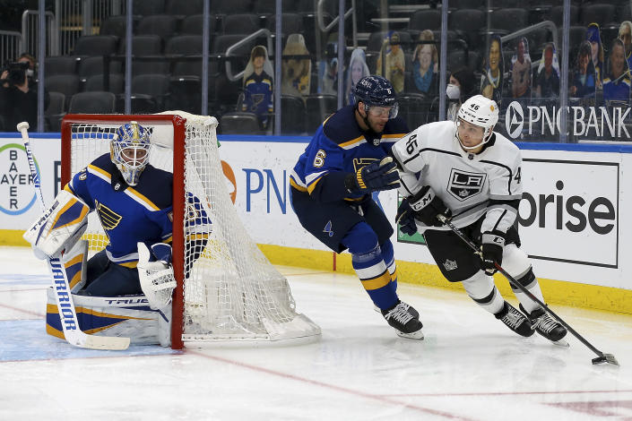 Los Angeles Kings' Blake Lizotte (46) controls the puck while under pressure from St. Louis Blues' Marco Scandella (6) while goaltender Jordan Binnington (50) watches during the third period of an NHL hockey game Wednesday, Feb. 24, 2021, in St. Louis. (AP Photo/Scott Kane)