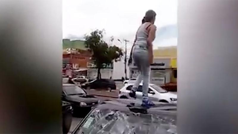 The woman screams across the street as she stamps on the roof of the car. Photo: Screenshot/Youtube