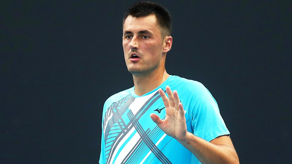 Bernard Tomic (pictured) raising his hand during Round 1 at the Australian Open.
