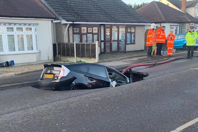 Emergency services at the scene assess the damage after a Toyota fell into a sinkhole in Essex that opened up in the early hours of Monday. (SWNS)
