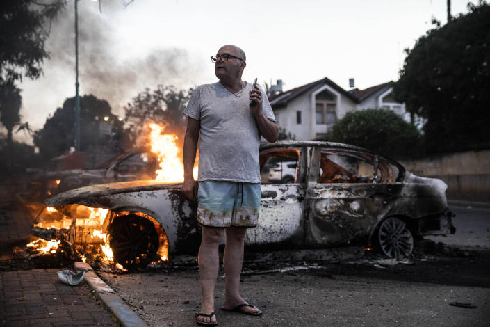 FILE - In this May 11, 2021, file photo, Jacob Simona stands by his burning car during clashes with Israeli Arabs and police in the Israeli mixed city of Lod, Israel. Israel is at war with Hamas, Jewish-Arab mob violence has erupted inside Israel, and the West Bank is experiencing its deadliest unrest in years. Yet this may all bolster Prime Minister Benjamin Netanyahu. (AP Photo/Heidi Levine, File)