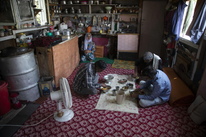 "Kashmiri man Ghulam Qadir Ota and family members eat a meal inside their house boat during lockdown to stop the spread of the coronavirus at a Nigeen Lake in Srinagar, Indian controlled Kashmir, July 24, 2020. ""We've not earned a single penny for a year now, all we have are these boats, We don't have any other means to earn,"" Ota said. Indian-controlled Kashmir's economy is yet to recover from a colossal loss a year after New Delhi scrapped the disputed region's autonomous status and divided it into two federally governed territories. (AP Photo/Mukhtar Khan)"