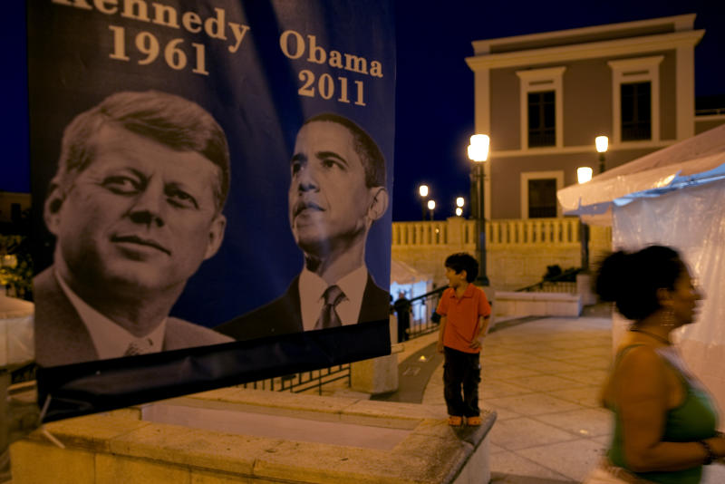A boy stands by a poster showing President Barack Obama and former President John F. Kennedy, a day before Obama's visit to Puerto Rico, on the grounds of El Morro National Park in San Juan, Puerto Rico, Monday June 13, 2011.  Obama's June 14 trip marks the first visit to the U.S. Territory by a sitting U.S. President since Kennedy's 1961 visit. (AP Photo/Ramon Espinosa)