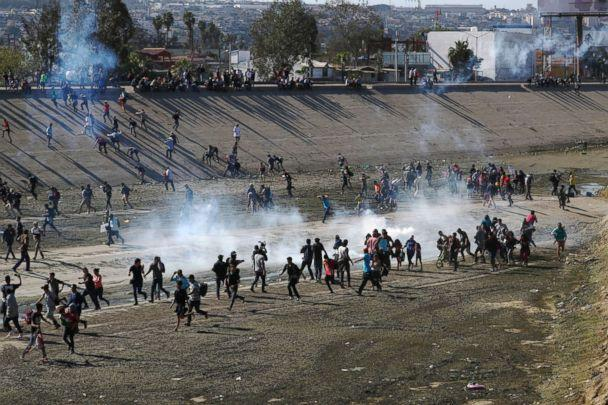 PHOTO: Migrants run from tear gas, thrown by the U.S border patrol, near the border fence between Mexico and the United States in Tijuana, Mexico, Nov. 25, 2018. (Hannah McKay/Reuters)