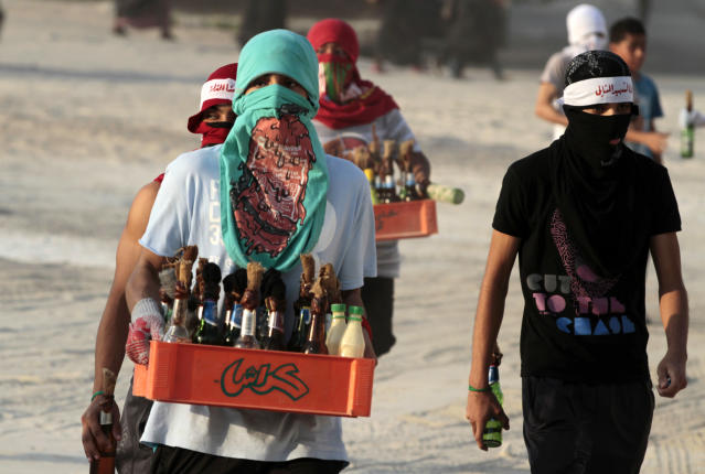 "Masked Bahraini anti-government protesters carry crates of homemade paint and petrol bombs into clashes with riot police in Sanabis, Bahrain, on Friday, Oct. 5, 2012. Riot police used water cannons and tear gas on Friday to disperse hundreds of anti-government protesters trying to reach a heavily guarded site that was once the hub of their uprising. The headband on the youth at right reads: ""I am the next martyr."" (AP Photo/Hasan Jamali)"