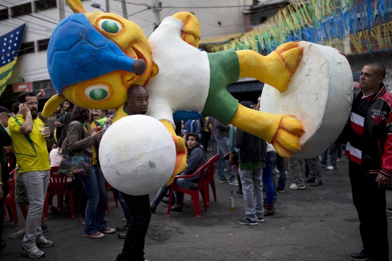 "Fans of the Brazilian national soccer team move a sculpture of the 2014 FIFA World Cup mascot ""Fuleco"", before a live telecast of the semi-finals World Cup soccer match between Brazil and Germany, in Sao Paulo, Brazil, Tuesday, July 8, 2014. Germany handed Brazil its heaviest World Cup loss ever with an astounding 7-1 rout in the semifinals that stunned the host nation. (AP Photo/Rodrigo Abd)"