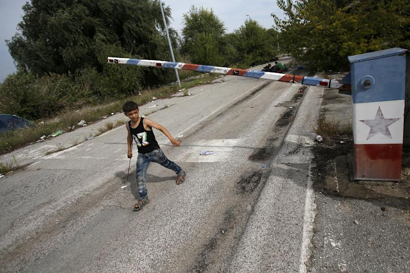 "FILE - In this file photo dated Thursday, Sept. 17, 2015, a migrant child walks at the ""Horgos 2"" border crossing that leads into Hungary, from Horgos, Serbia, with the old Yugoslav communist flag on the abandoned border point. Europe's open borders seem to symbolize liberty and forward thinking, but they increasingly look like the continent's Achilles' heel, with its inability to implement cross border security. (AP Photo/Darko Vojinovic, FILE)"