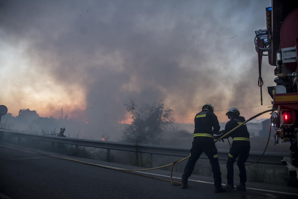 GRANADA, SPAIN - JULY 12: Two firefighters prepare the rubber to put out the fire along the Viznar road on July 12, 2021 in Granada, Spain. A fire in an area between Granada, Jun and Viznar has forced the activation of emergency level 1, due to high temperatures and the force of the wind. Scientists have warned that climate change will cause huge forest fires, even with just a 0.5 degree rise in temperatures. (Photo by Carlos Gil Andreu/Getty Images)